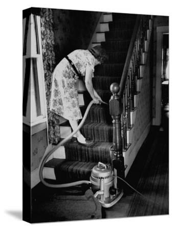 Housewife Cleaning Her Carpet with Vacuum Cleaners-Yale Joel-Stretched Canvas Print