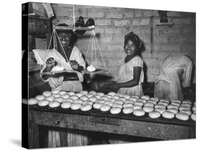 Women Stacking Loaves of Bread on Wooden Table, in Primitive Village of Zoogocho--Stretched Canvas Print