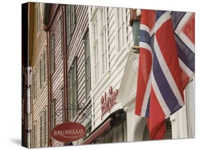 Wooden Merchants Premises and Norwegian Flag, Bryggen Old Harbour Side, Bergen, Norway, Scandinavia-James Emmerson-Stretched Canvas Print
