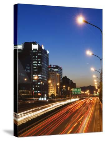 Car Light Trails and Modern Architecture on a City Ring Road, Beijing, China-Kober Christian-Stretched Canvas Print