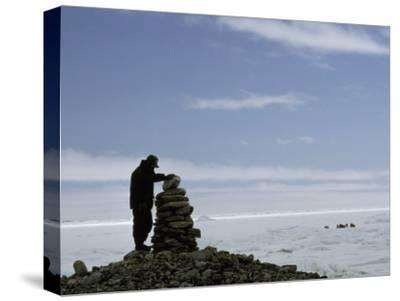 Inuit Hunter Surveys a Sacred Inuksuk Monument, Used as a Waypost-Gordon Wiltsie-Stretched Canvas Print