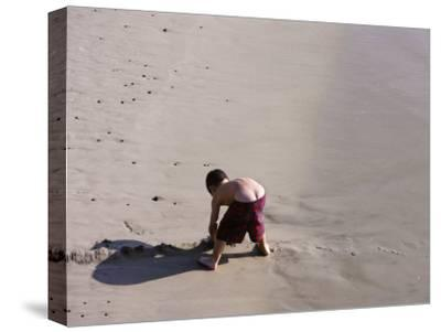 Boy's Bottom Peeks Out from His Bathing Suit as He Plays in Sand-White & Petteway-Stretched Canvas Print
