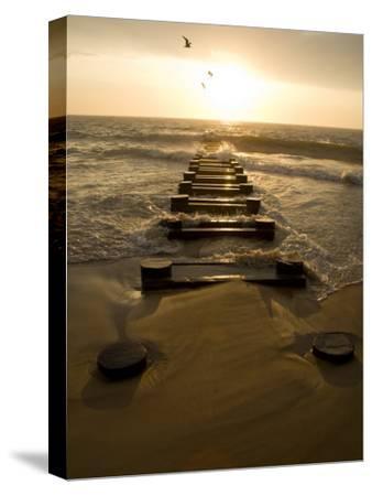 Atlantic Ocean Waves Break Against Pilings at Sunrise-Stephen St^ John-Stretched Canvas Print