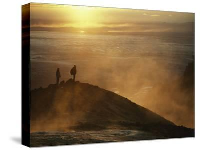 Two Silhouetted Men at Twilight Amid Geothermal Steam on Mountain Top-Paul Chesley-Stretched Canvas Print