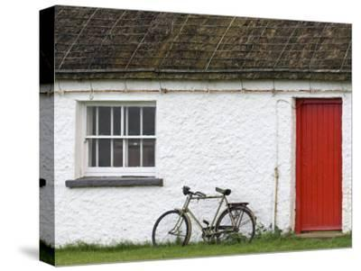 Historic Thatched Roof House with a Red Door and Old Bicycle-Rich Reid-Stretched Canvas Print