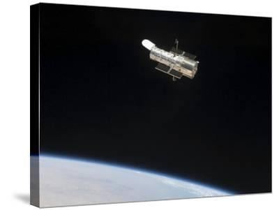 The Hubble Space Telescope in Orbit Above Earth--Stretched Canvas Print