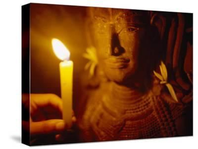Man Holds a Candle Up to a Stone Carving at the Angkor Wat Temple-xPacifica-Stretched Canvas Print