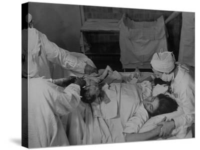"""Nurse at Her Head and Holding Her Hands, as She Gazes at Her Baby Boy after """"Painless"""" Childbirth-Alfred Eisenstaedt-Stretched Canvas Print"""