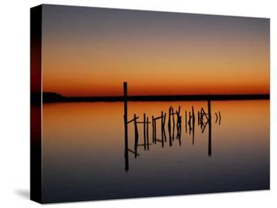 Sunset over Calm Water and a Dilapidated Old Pier-Ross Kelly-Stretched Canvas Print