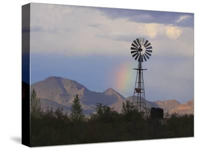 A Windmill on a Ranch with a Rainbow and Mountain Scenery-George Grall-Stretched Canvas Print