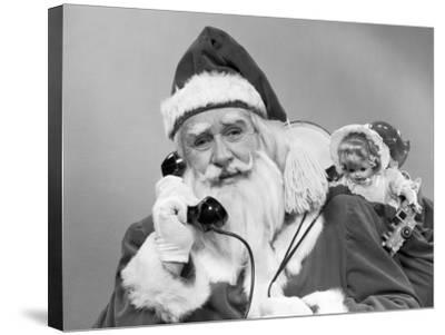 Santa Claus on the Telephone With His Sack of Toys on His Back-H^ Armstrong Roberts-Stretched Canvas Print