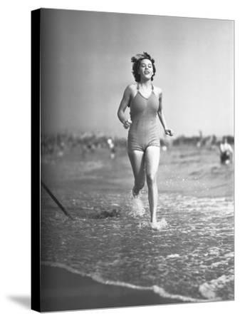 Woman in Swimsuit Running on Shoreline-George Marks-Stretched Canvas Print