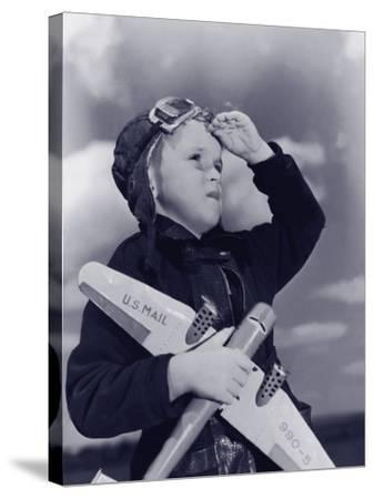 Boy (8-10) Wearing Flying Cap and Goggles Holding Toy Plane--Stretched Canvas Print
