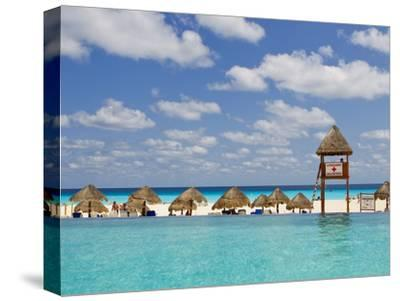 The Caribbean Sea, Tiki Huts and a Lifeguard Stand from a Resort Pool-Mike Theiss-Stretched Canvas Print