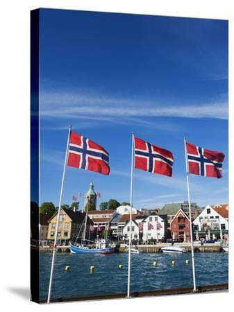Norwegian Flags and Historic Harbour Warehouses, Stavanger, Norway, Scandinavia, Europe-Christian Kober-Stretched Canvas Print