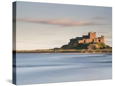 Bamburgh Castle Bathed in Golden Evening Light Overlooking Bamburgh Bay with the Sea Filling the Fo-Lee Frost-Stretched Canvas Print