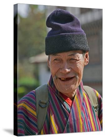 An Old Man at Trashigang Wearing the Traditional Gho Robe of All Bhutanese Men-Nigel Pavitt-Stretched Canvas Print