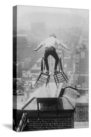 Reynolds Performs a Balancing Act on Roof in New York City--Stretched Canvas Print