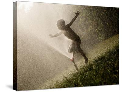 A Boy Plays in a Sprinkler on a Hot Summer Day-Heather Perry-Stretched Canvas Print