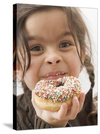 Girl Holding a Doughnut with Sprinkles, Partly Eaten--Stretched Canvas Print