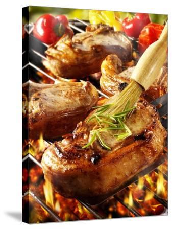 Brushing Pork Chop on Barbecue Rack with Oil-Paul Williams-Stretched Canvas Print
