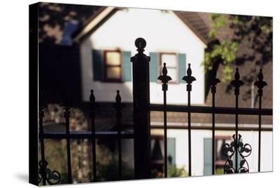 A Wrought Iron Black Fence Frames a Home with Blue Shuttered Windows-Paul Damien-Stretched Canvas Print