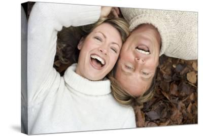 Laughing Couple Lying on Autumn Leaves-Ian Boddy-Stretched Canvas Print
