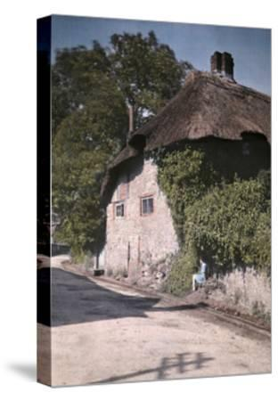 A Girl Sits on a Wall Next to an Old Thatched Cottage-Clifton R^ Adams-Stretched Canvas Print
