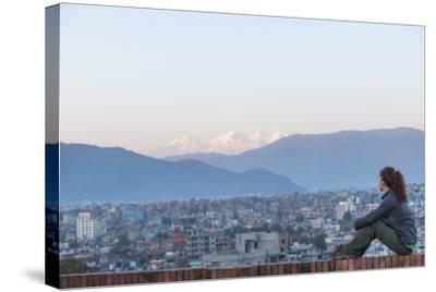 A Woman Sits on a Rooftop in Kathmandu and with the Ganesh Himal Mountain Range in the Distance-Alex Treadway-Stretched Canvas Print