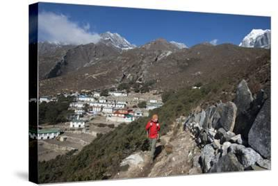 A Hiker Walks Past a Wall of Mani Stones Inscribed with an Ancient Tibetan Mantra-Alex Treadway-Stretched Canvas Print