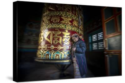 An Old Tibetan Woman Spins a Prayer Wheel While Counting Through a String of Rosary Beads-Alex Treadway-Stretched Canvas Print