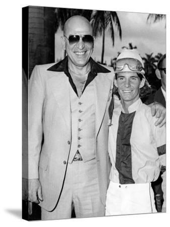 Actor Telly Savalas Poses with a Jockey at Hialeah Park, C.1970--Stretched Canvas Print