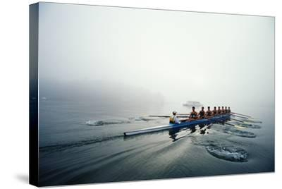 Rowing Team on Lake in Early Morning Fog-Nick Wilson-Stretched Canvas Print