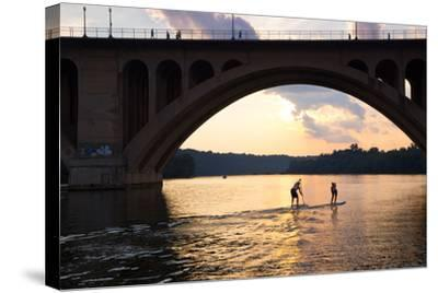 Paddleboarders Glide on the Potomac River under the Key Bridge in Georgetown-Skip Brown-Stretched Canvas Print