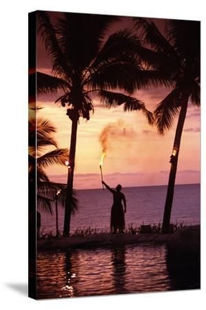 Native in a Grass Skirt Holding a Flaming Torch by Coast at Sunset-Design Pics Inc-Stretched Canvas Print