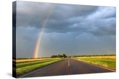 A Thunderstorm Produces a Vivid Rainbow Next to a Rain-Soaked Paved Road-Jim Reed-Stretched Canvas Print