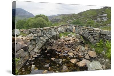 Ancient Arched Stone Bridge across Mountain Stream--Stretched Canvas Print