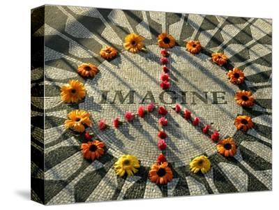 A Makeshift Peace Sign of Flowers Lies on Top John Lennon's Strawberry Fields Memorial--Stretched Canvas Print