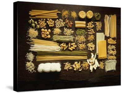 Many Different Types of Pasta on Dark Wooden Background-Walter Cimbal-Stretched Canvas Print