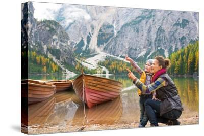 Happy Mother and Baby Pointing on Copy Space While on Lake Braies in South Tyrol, Italy-Mr Alliance-Stretched Canvas Print
