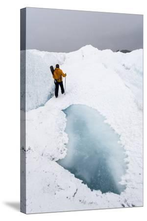 A Hiker Passing Between a Dangerous Crevasse and a Melt Pond on the Greenland Ice Shelf-Jason Edwards-Stretched Canvas Print