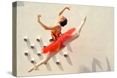 A Ballerina Dancing and Leaping Wearing a Red Dress-Kike Calvo-Stretched Canvas Print