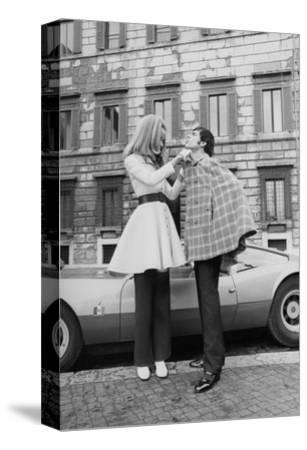 Vogue - April 1969 - Veruschka Adjusts Tomas Milian's Cape-Franco Rubartelli-Stretched Canvas Print