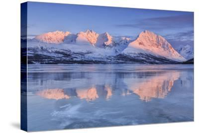 Snowy Peaks are Reflected in the Frozen Lake Jaegervatnet at Sunset, Lapland-Roberto Moiola-Stretched Canvas Print