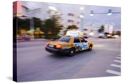 Taxi at Full Speed Early in the Evening on Collins Avenue, Miami South Beach, Florida-Axel Schmies-Stretched Canvas Print