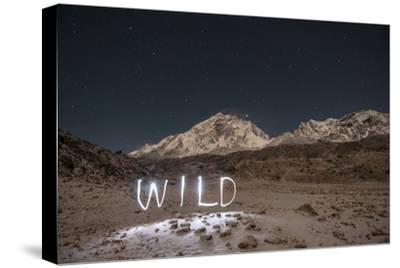 """A Time Exposure of the Word """"Wild"""" Written Beneath the Peak of Mount Everest-Max Lowe-Stretched Canvas Print"""