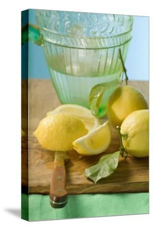 Fresh Lemons with Leaves in Front of Water Jug-Foodcollection-Stretched Canvas Print