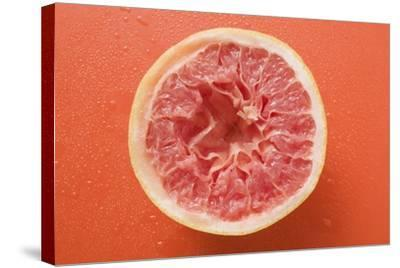 Squeezed Pink Grapefruit on Orange Background-Foodcollection-Stretched Canvas Print