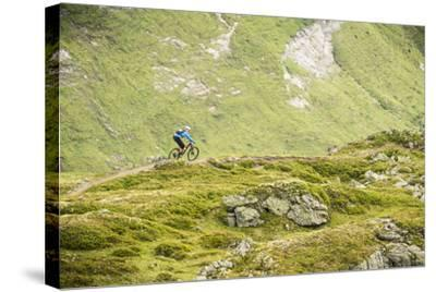 Mountain Biker In The Swiss Alps-Axel Brunst-Stretched Canvas Print