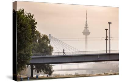 Mannheim, Baden-Württemberg, GER: Male Running Over Bridge Crossing River Neckar On Foggy Morning-Axel Brunst-Stretched Canvas Print